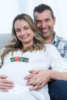 Schwangere frau mit babywürfeln auf ihrem bauch und mann, die zu hause auf einem sofa sitzen