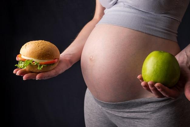 Schwangere frau mit bauch, der einen burger und einen apfel hält