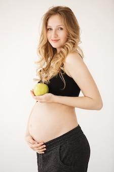 Schwangere frau mit blonden haaren in bequemen schwarzen kleidern lächelnd