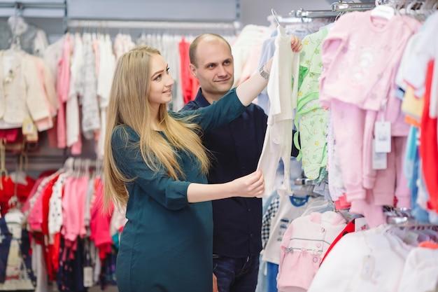 Schwangere frau mit dem ehemanneinkaufen für baby.