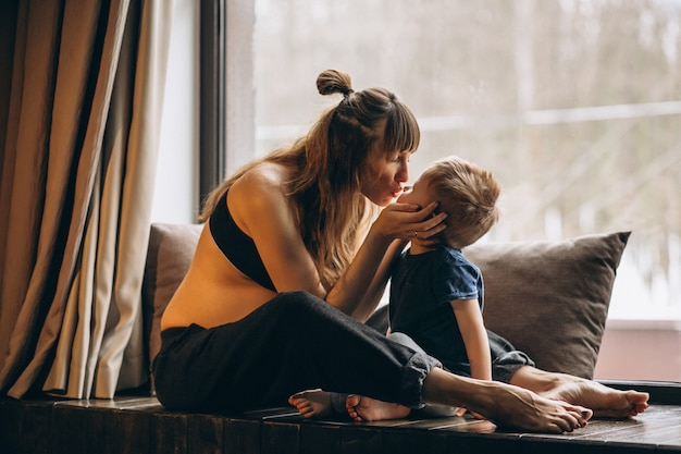 Schwangere frau mit dem sohn, der am fenster sitzt