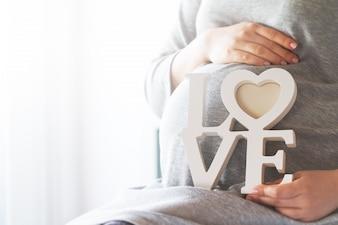 """Schwangere Frau mit dem Wort """"Liebe"""""""