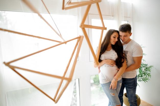 Schwangere frau mit ehemann vor dem fenster
