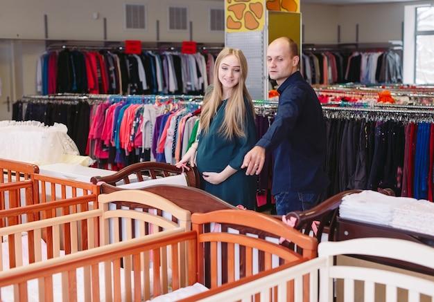 Schwangere frau mit ehemann wählt ein babybett im speicher.