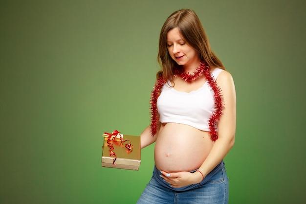 Schwangere frau mit einem geschenk, das an heiligabend ein geschenk für ein baby an einem neuen jahr bekommt