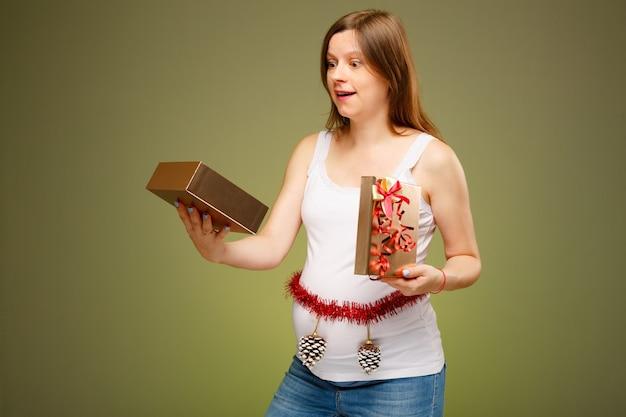 Schwangere frau mit einem geschenk überraschten gesichtsausdruck, der an heiligabend ein geschenk bekommt