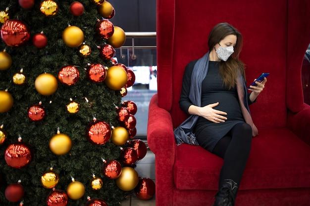 Schwangere frau mit einer gesichtsmaske, die drinnen eine sms sendet