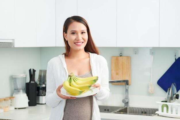 Schwangere frau mit frischen bananen