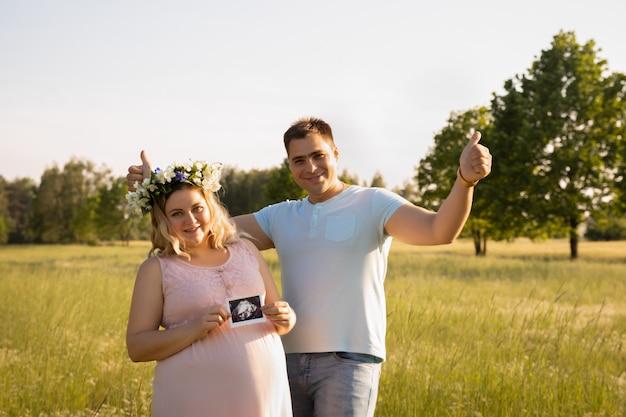 Schwangere frau mit ihrem ehemann auf einem feld mit blumen.