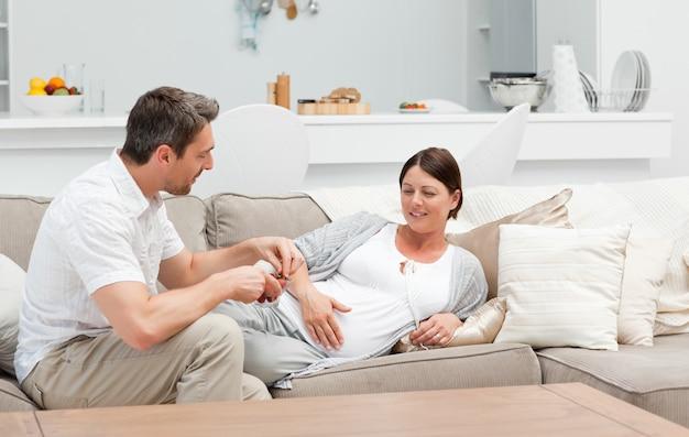 Schwangere frau mit ihrem ehemann, der erdbeere isst