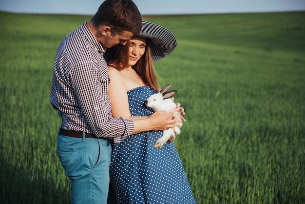 Schwangere frau mit ihrem mann und kaninchen