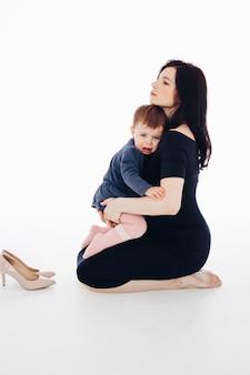 Schwangere frau mit kleiner tochter auf den händen, die im weißen studio sitzen. schwangerschafts- und mutterschaftskonzept. foto in hoher qualität Premium Fotos