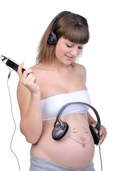 Schwangere frau mit kopfhörern auf dem bauch.