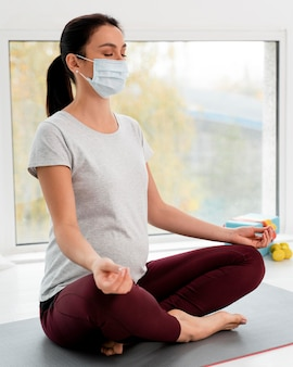 Schwangere frau mit medizinischer maske, die yoga tut