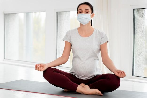 Schwangere frau mit medizinischer maske meditieren