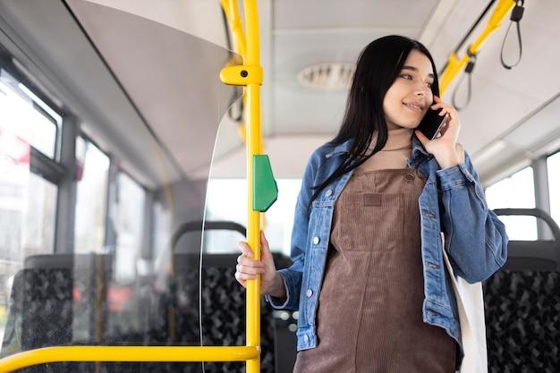 Schwangere frau mit mittlerer aufnahme, die am telefon telefoniert