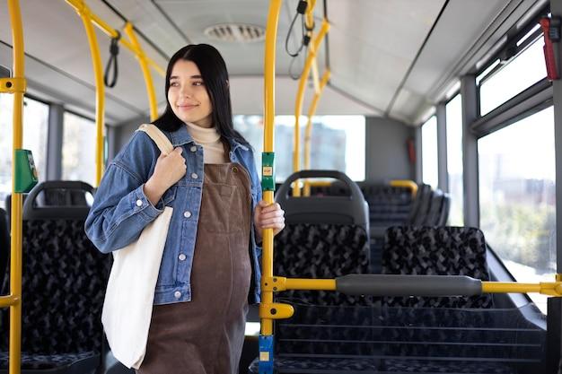 Schwangere frau mit mittlerer aufnahme, die mit dem bus reist