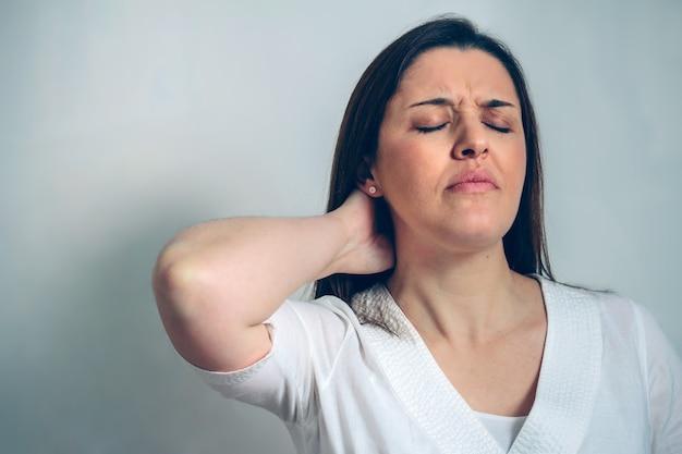 Schwangere frau mit nackenschmerzen, die ihren hals berührt