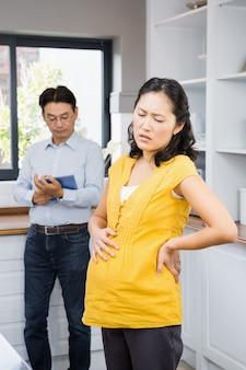 Schwangere frau mit rückenschmerzen in der küche