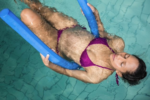 Schwangere frau mit schaumrolle im pool