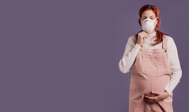 Schwangere frau mit schutzmaske