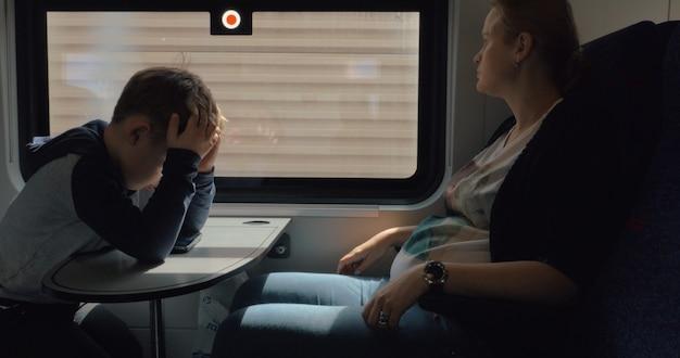 Schwangere frau mit sohn, die mit dem zug reist