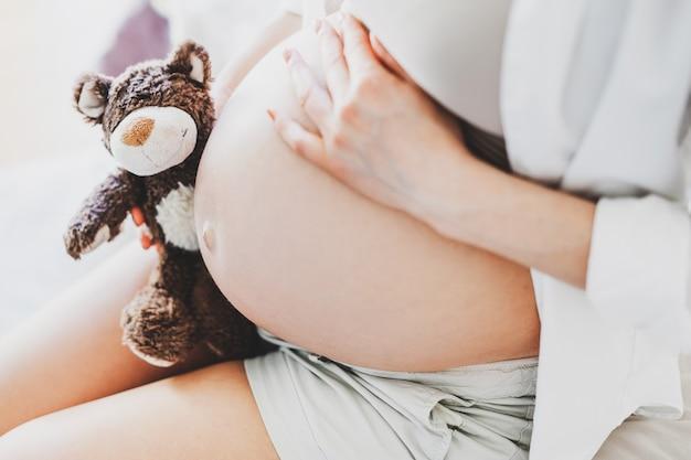 Schwangere frau mit spielzeug-teddybär, der baby hört