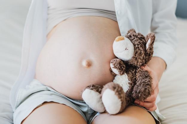 Schwangere frau mit spielzeug teddybär hören baby