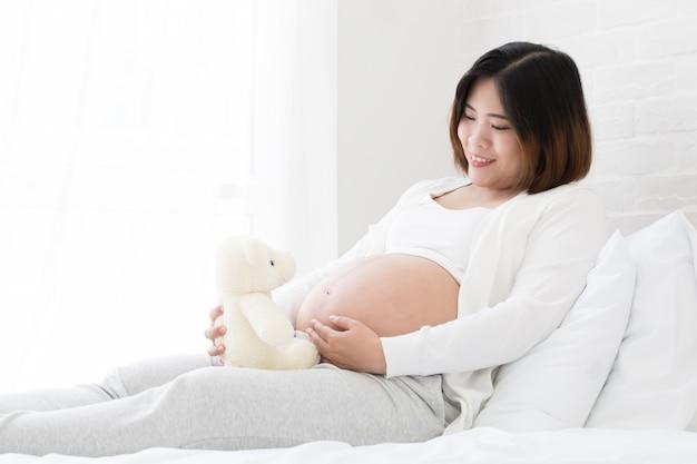 Schwangere frau mit teddybär auf weißem bett.