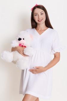 Schwangere frau mit teddybär trägt schönes kleid