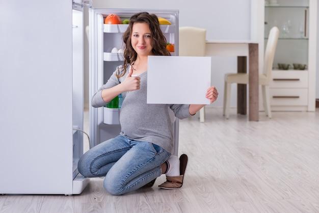 Schwangere frau nahe kühlschrank mit leerer mitteilung