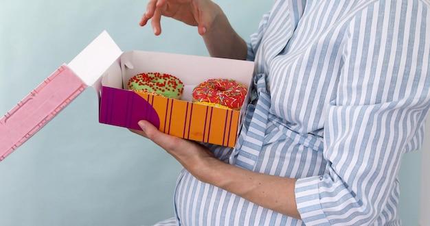 Schwangere frau öffnet eine schachtel brötchen und isst leckere donuts im sitzen.
