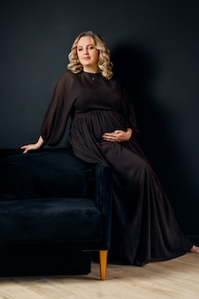 Schwangere frau posiert in einem eleganten schwarzen kleid drinnen studio schwarzer wandhintergrund blonde kaukasische frau mittleren alters sechs monate schwangerschaft