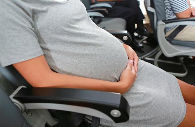 Schwangere frau reist mit dem flugzeug, das am sitz sitzt.