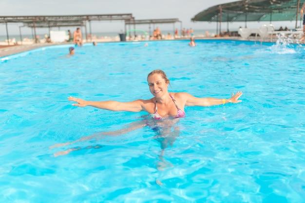 Schwangere frau schwimmt in einem baseen auf dem rücken