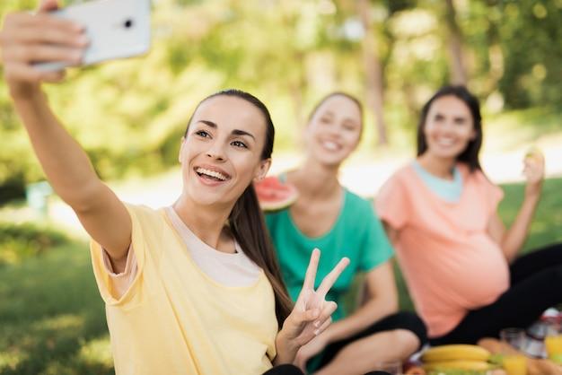 Schwangere frau sitzt auf einem picknick und macht selfies.