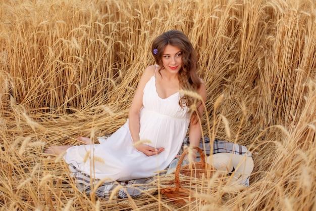 Schwangere frau sitzt in einem weizenfeld ein picknick