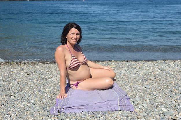 Schwangere frau sitzt und sonnt sich am strand