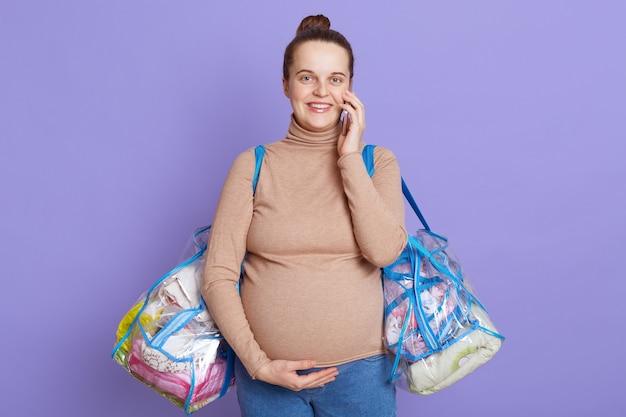 Schwangere frau spricht am handy und lächelt