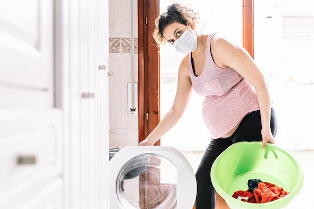 Schwangere frau trägt eine maske im gesicht, um viren beim laden einer wäsche vorzubeugen