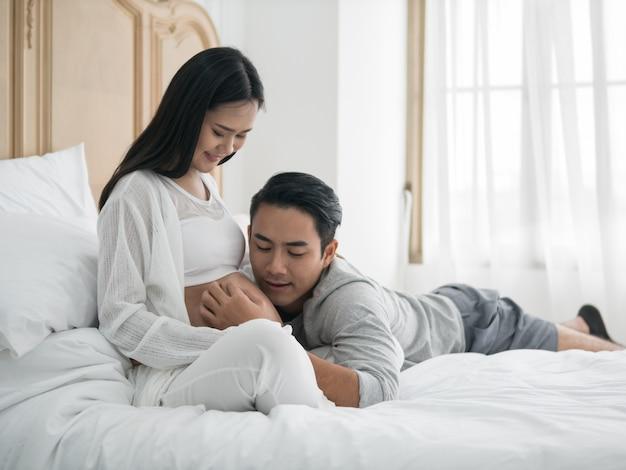 Schwangere frau und ehemann des asiaten, die auf das bett beim zeit zusammen verbringen legt.
