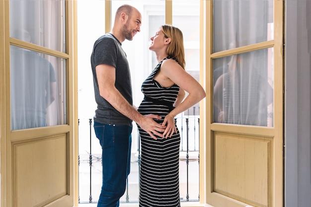 Schwangere frau und ehemann vor offenen fenstern