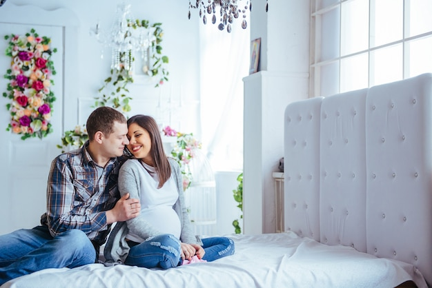 Schwangere frau und ihr ehemann, die beuten hält