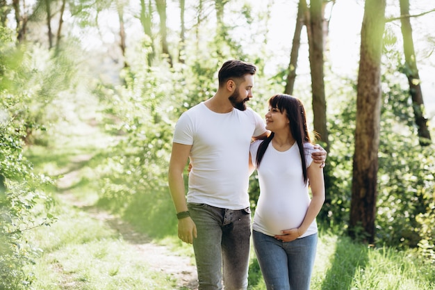 Schwangere frau und ihr geschlagener ehemann, die zusammen auf dem bauch in der natur im freien umarmt