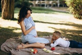 Schwangere Frau und ihr kleiner Sohn, die Picknick im Park haben