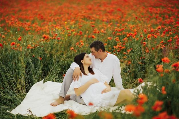 Schwangere frau und ihr mann liegen auf weißem plaid im roten mohnfeld