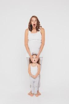 Schwangere frau und kleines mädchen in der sportkleidung