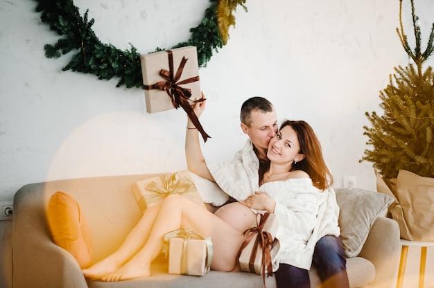 Schwangere frau und mann bedeckt mit plaid in der nähe von weihnachtsbaum zu hause frohe weihnachten