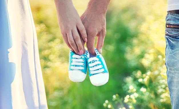 Schwangere frau und mann halten babyschuhe