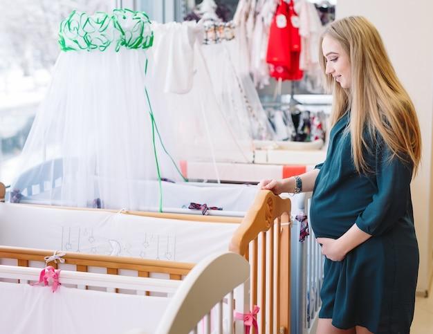 Schwangere frau wählt ein babybett im speicher.